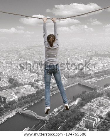 A woman hanging on a rope over the Paris - stock photo