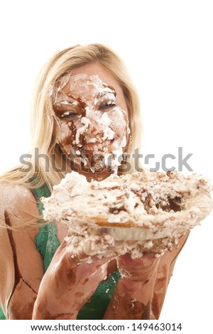 A woman has pie all over her face and is very messy