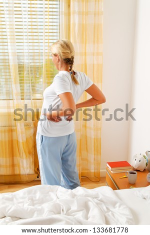 a woman has the morning after waking up pain. - stock photo