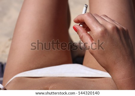 A woman having a cigarette on the beach - stock photo
