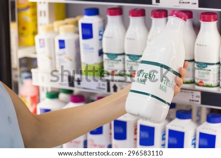 A woman having on her hands a fresh milk bottle in supermarket - stock photo