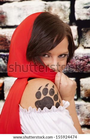 A woman hiding being her red hood with her paw print on her arm showing. - stock photo