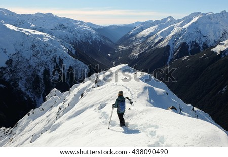 A Woman Hiker Descends a Snowy Peak with Mountain Views and River Canyon Beyond.  Mt Bealey, Arthurs Pass, Southern Alps, Canterbury, New Zealand - stock photo