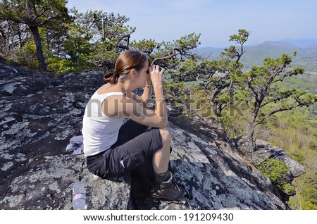 A woman hiker on a rock overlook using her binoculars.  Cell phone on her pocket.