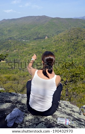 A woman hiker sitting on a mountain overlook pointing at a landmark.  - stock photo