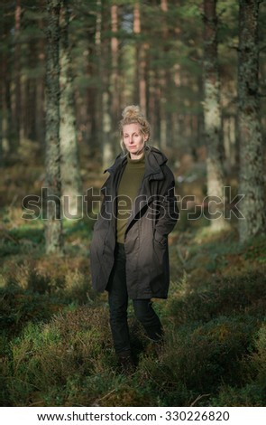 A woman hiker walking through a pine forest in Scotland