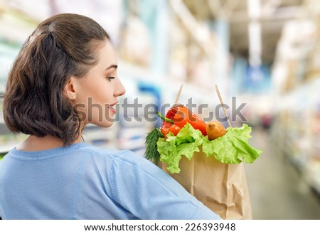 a woman holding a bag of fruit