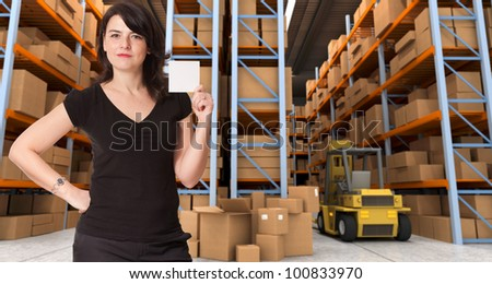 A woman holding a blank paper in a distribution warehouse, ideal for inserting your own message - stock photo