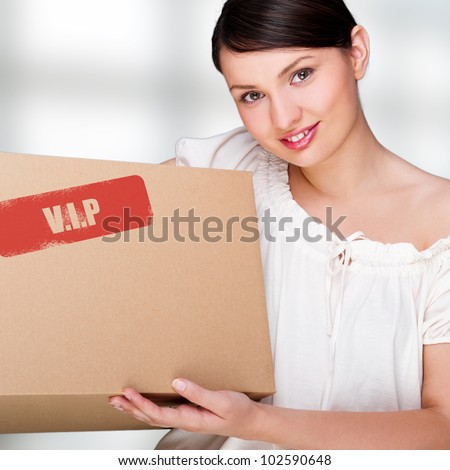 A woman holding a box inside office building or home interior. Package sign on box - stock photo