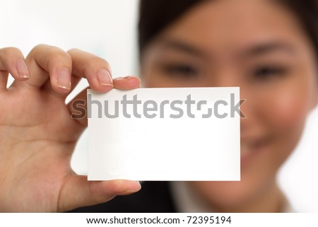 A woman holding a card with her face out of focus - stock photo