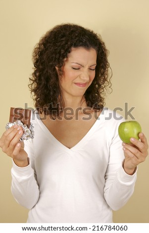 A woman holding a chocolate and an apple. - stock photo