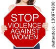A woman holding a conceptual stop sign on violence against women - stock photo
