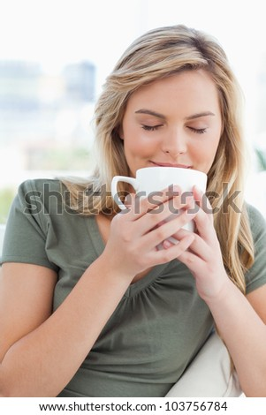 A woman holding a cup up to her nose, taking in a smell of the cups contents in front of her.