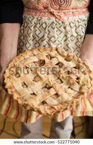 A woman holding a fresh baked apple pie.