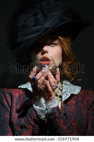 A woman holding a glass of red wine