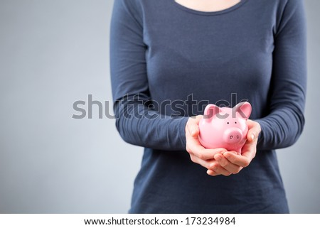 A woman holding a pink piggy bank, copy space next to her. - stock photo