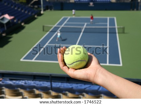 A woman holding a tennis ball with a match in the background - stock photo