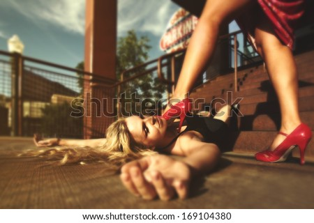 a woman holding her foot on another woman - stock photo