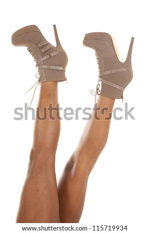 A woman holding her shoes high up in the sky . - stock photo