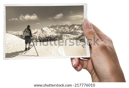 A woman holding old photos of skier with traditional old wooden skis - stock photo