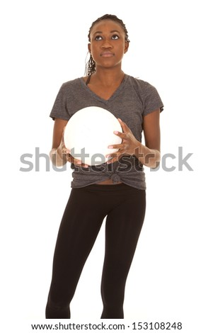 a woman holding on to a volleyball looking up. - stock photo