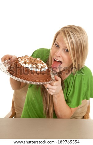 a woman holding on to her chocolate cake, getting ready to lick the frosting.