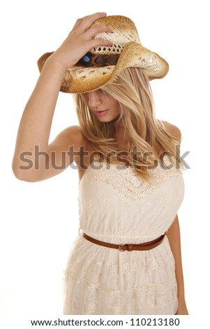 A woman holding on to her cowgirl hat looking down. - stock photo