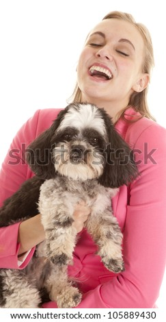 A woman holding on to her dog laughing. - stock photo