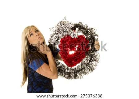 A woman holding on to her heart wreath with a pucker on her lips.  - stock photo