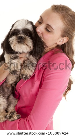 A woman holding on to her little dog kissing his ear. - stock photo