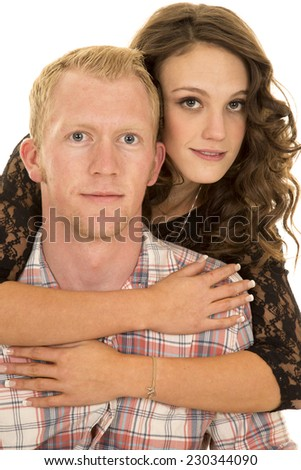 A woman holding on to her man around his shoulders. - stock photo