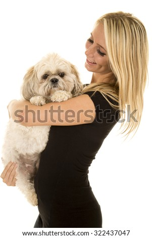 a woman holding on to her puppy with a smile.