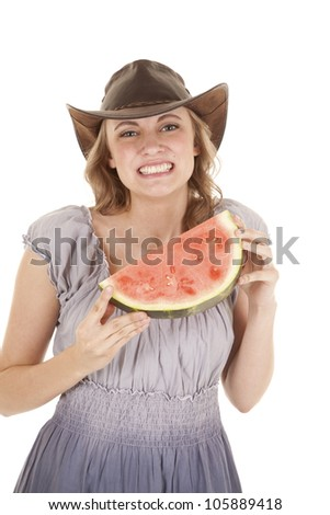 A woman holding on to her watermelon with  a smile on her face. - stock photo