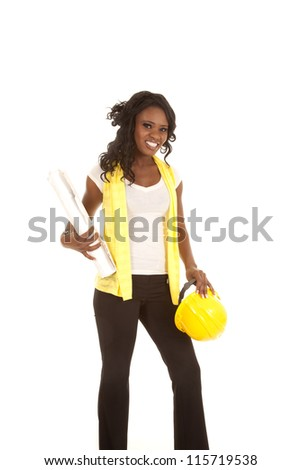 a woman holding on to her yellow hard hat and her blue prints with a smile on her face