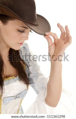 A woman holding on to the brim of her hat looking down. - stock photo
