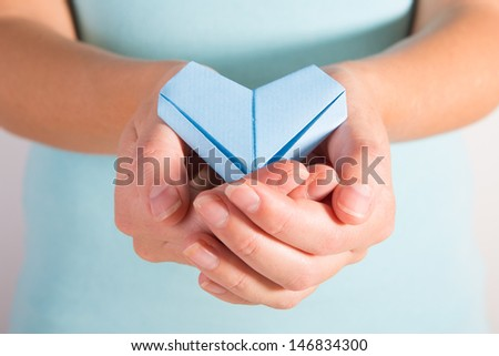 A woman holding out a blue origami heart in cupped hands - stock photo