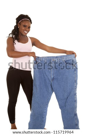 a woman holding out her big pants with a big smile - stock photo