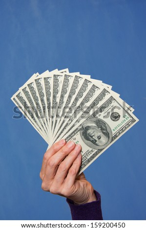 A woman holds a handful of cash - stock photo