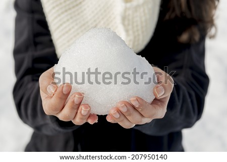 A woman holds a huge snowball in bare hands in shallow focus