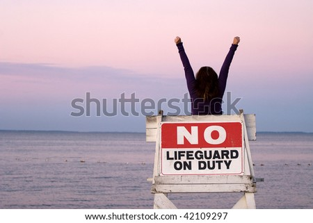 A woman holds her arms up in the air while seated in a vacant lifeguard chair at the beach. - stock photo