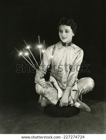 A woman holds sparklers - stock photo