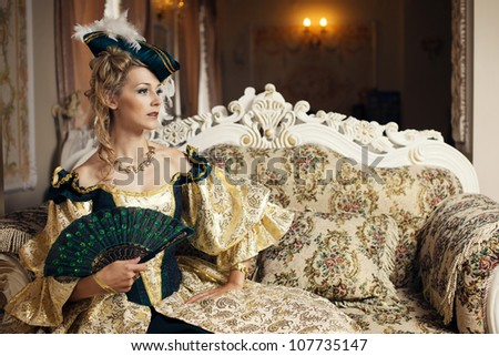 A woman in a ball gown sits