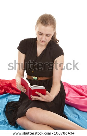 A woman in a black dress is sitting and reading a book. - stock photo