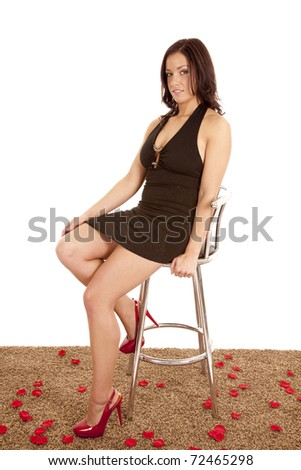 A woman in a black dress is sitting on a stool by some rose pedals. - stock photo