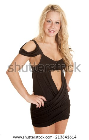 A woman in a black short dress, showing off her body.  She has her hands on her hips and a smile on her face