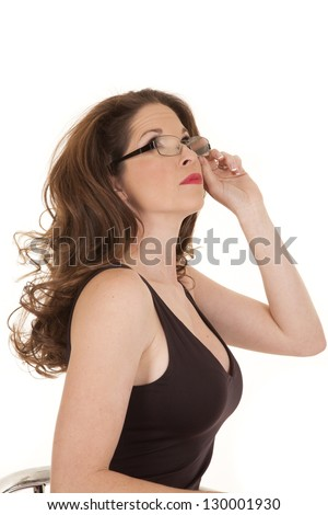 A woman in a black tank top holds her glasses and looks up to the side. - stock photo