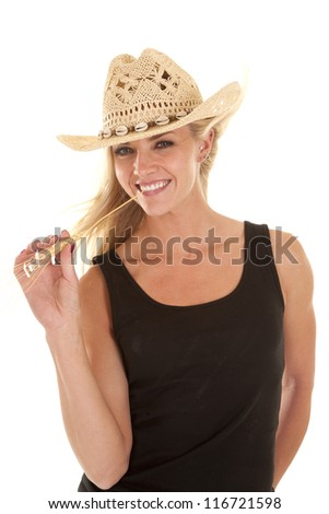 A woman in a cowboy hat and a black tank top has a piece of wheat in her mouth and smiling. - stock photo