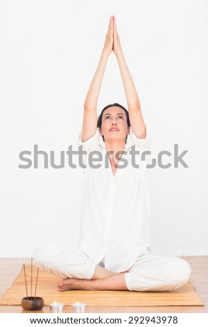 a woman in a meditation position against a white background - stock photo