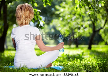 A woman in a park in the lotus position - stock photo