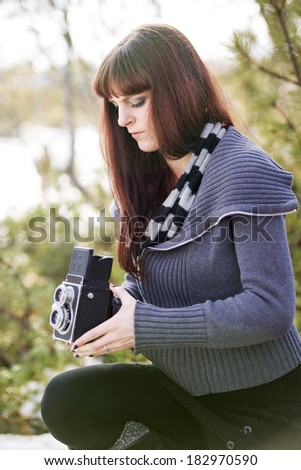 A woman in a park taking a photo with a twin lens camera